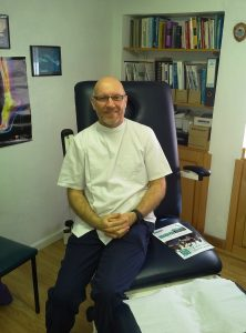 Jonathan Small Podiatrist at Health First Southam sitting in a treatment chair
